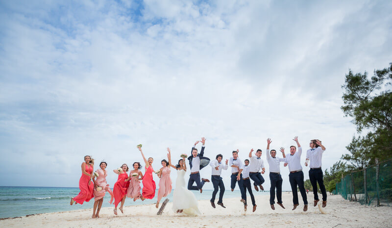 Bridal party jumping on beach in Riviera Maya