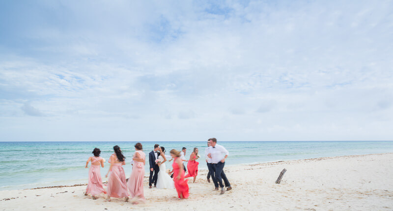 Bridal party running around bride and groom on beach in Riviera Maya