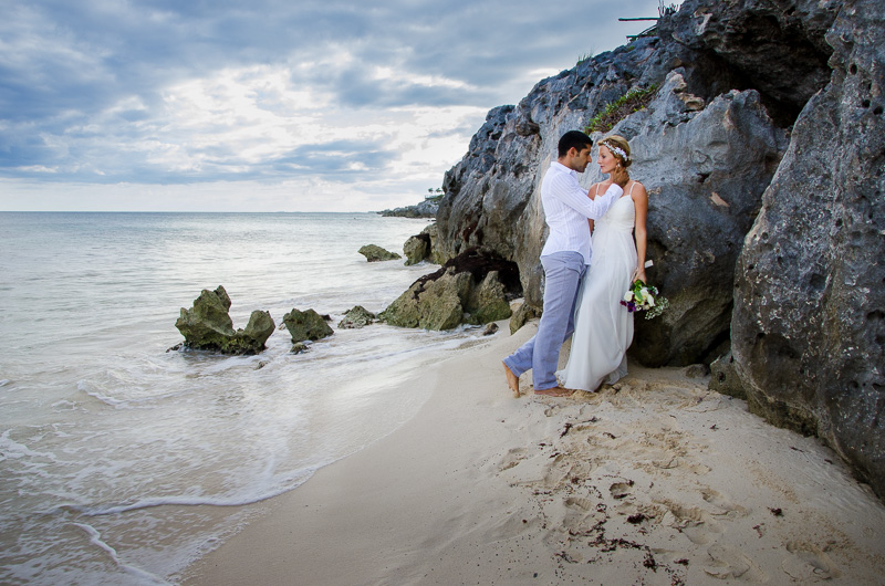Bride and groom in romantic pose on bean in Tulum wedding