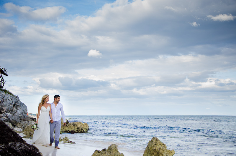 Groom and bride walking on the shore at Tulum beach wedding