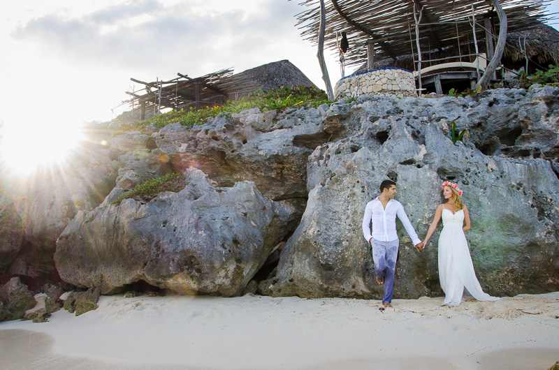 Bride and Groom standing by rocky formation for Tulum wedding photography
