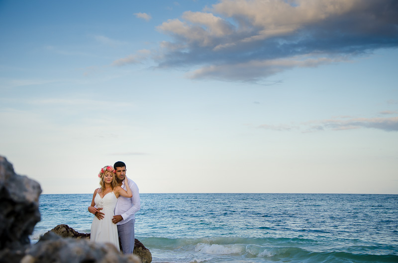 Couple posing by the ocean at Tulum beach wedding