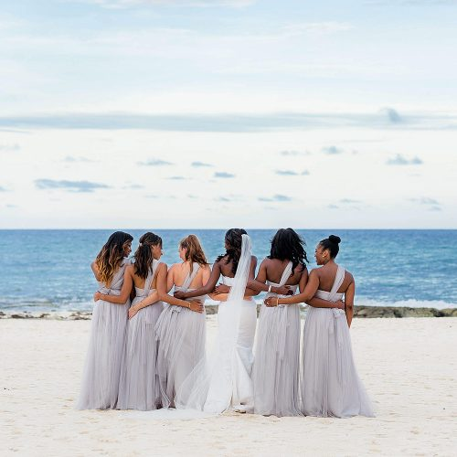 Bridesmaids arm in arm after wedding at Iberostar Grand Hotel Paraiso