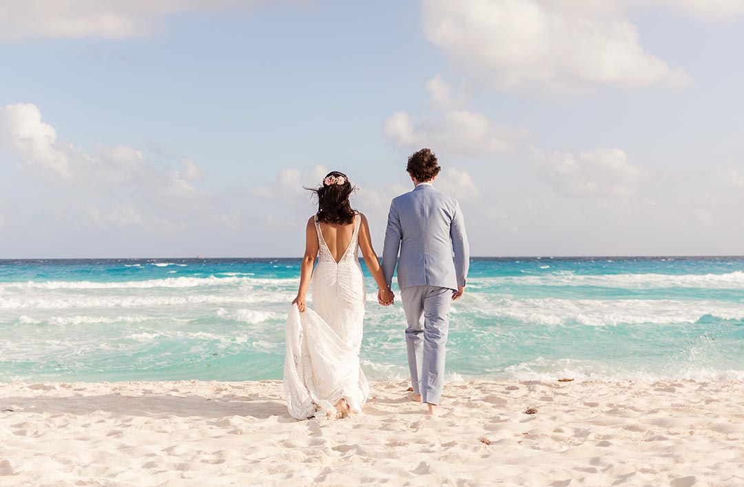 Bride and Groom holding hands walking on beach in Cancun