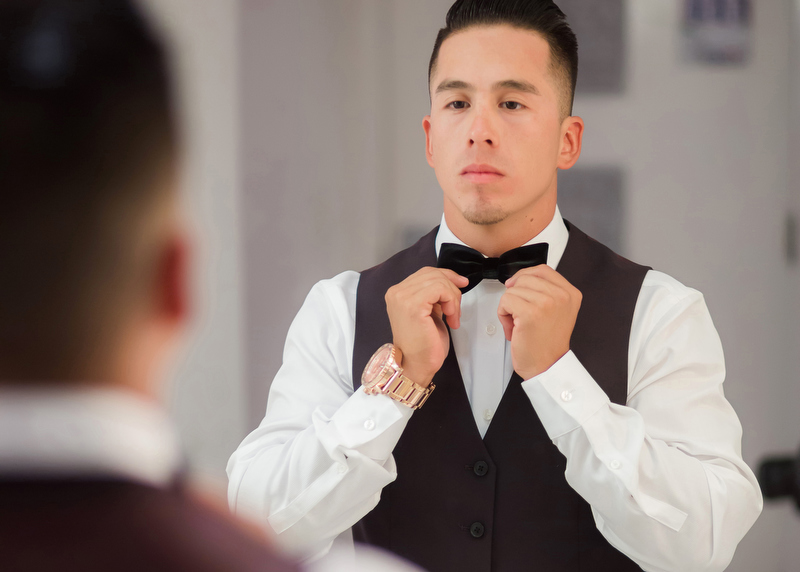 Groom doing up tie in mirror.
