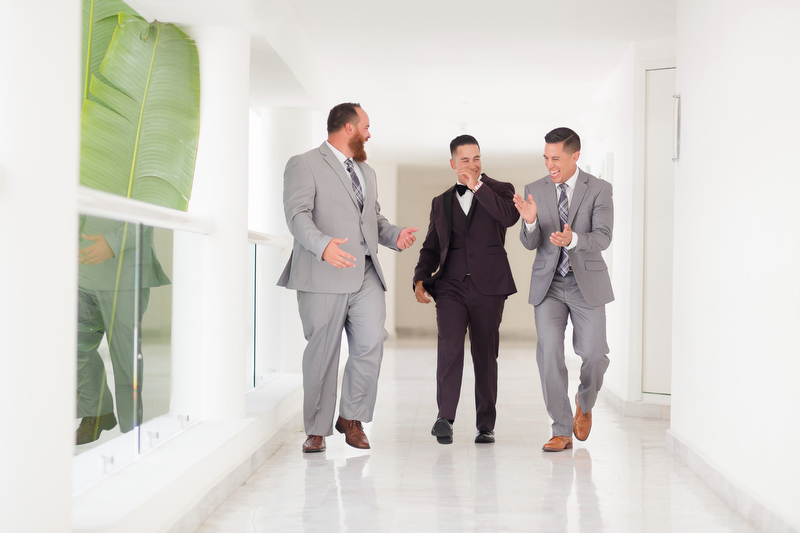 Groomsmen walking in hallway at Playacar Palace Resort
