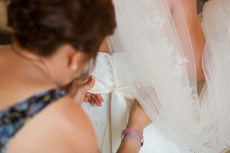 Close up of mother doing up wedding dress.