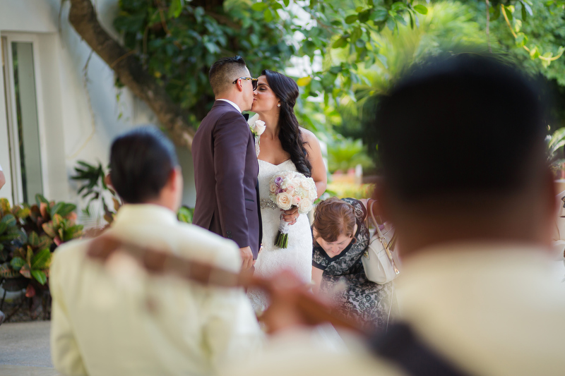 Bride and groom kissing around mariachi band.