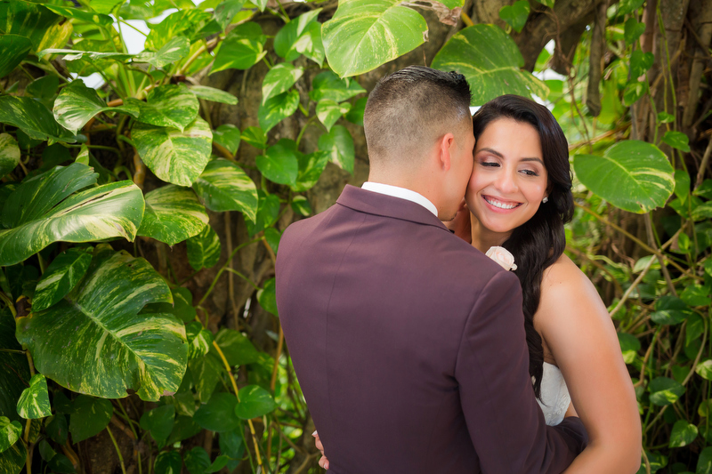 Groom kissing bride in garden at Playacar Palace Resort