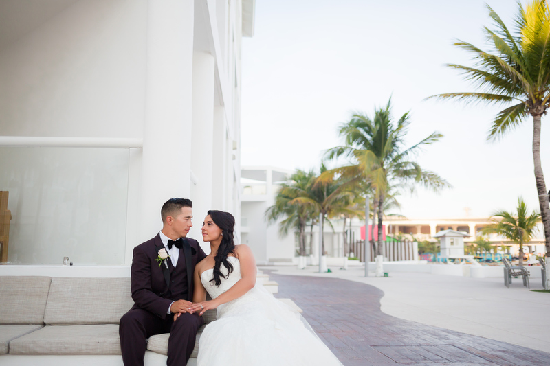 Bride and groom sitting on bench at Playacar Palace Resort