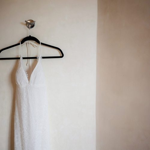 Wedding dress hanging on wall.