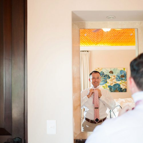 Groom looking in mirror getting ready for wedding.