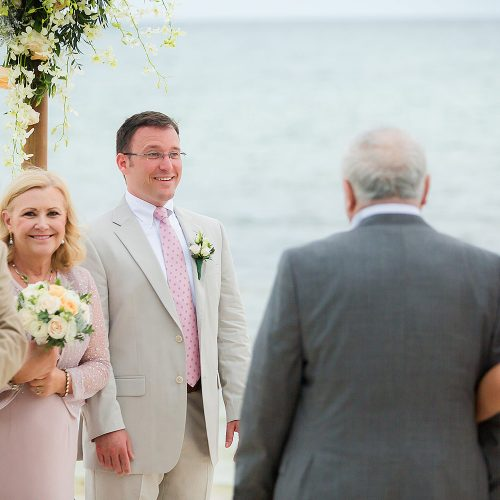 Groom watching bride walk down aisle on beach.