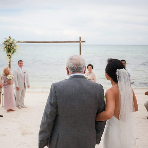 Bride and father walking down beach in Tulum