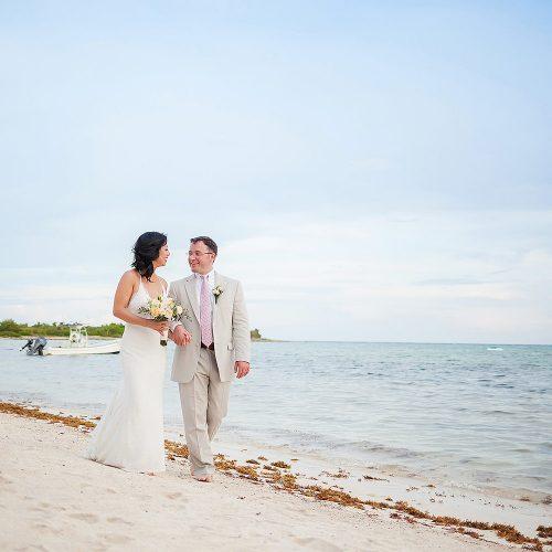 Bride and groom walking on beach in Tulum