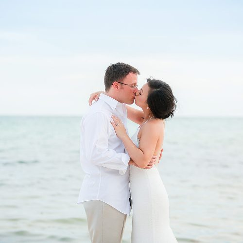 Bride and groom kissing on beach in Tulum