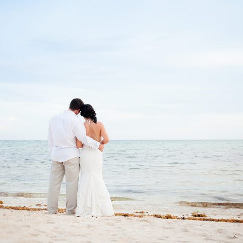 Bride and groom looking out at ocean in Tulum