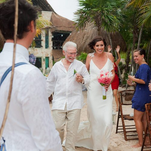 Bride walking down beach as it starts to rain in Riviera Maya