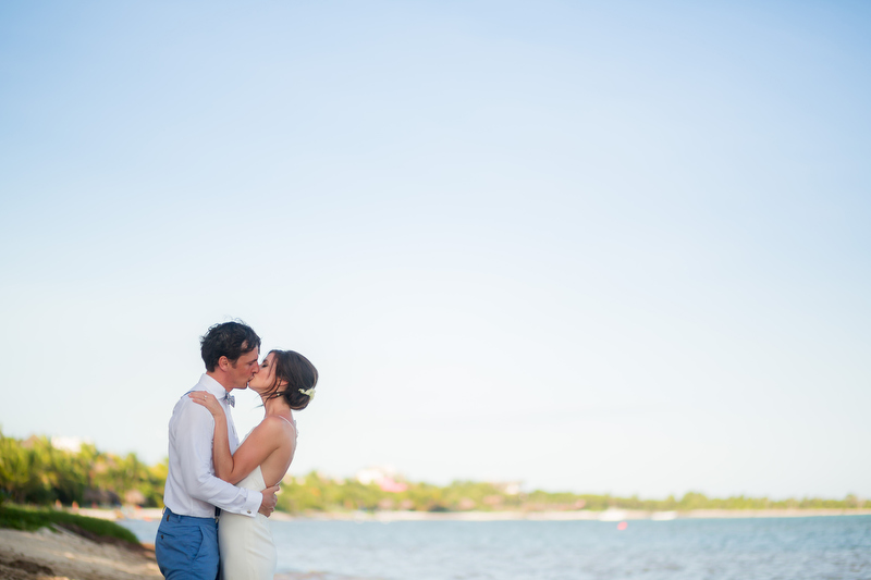 Bride and groom kissing on beach, Solomin Bay