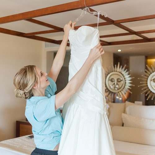 Bride hanging wedding dress at Excellence Playa Mujeres
