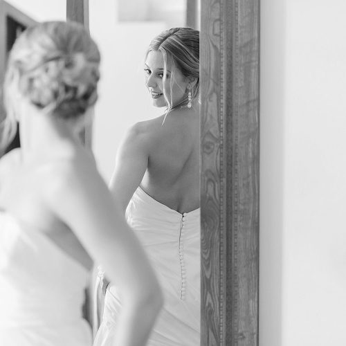 Bride looking at herself in mirror before wedding at Excellence Playa Mujeres