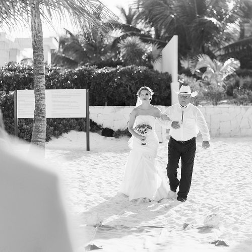 Bride walking down aisle at beach wedding ceremony at Excellence Playa Mujeres