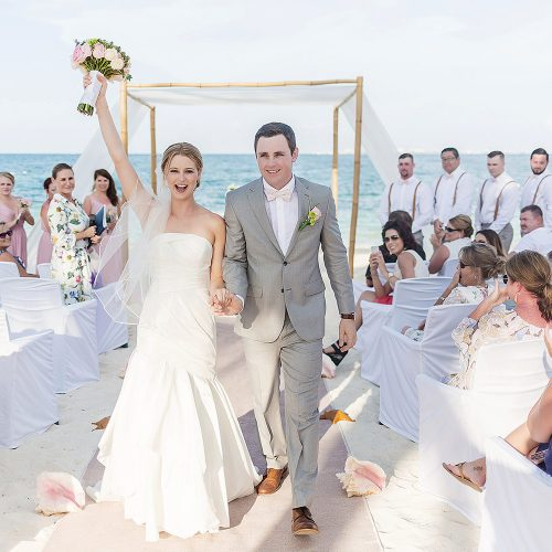 Bride and groom celebrate after wedding atExcellence Playa Mujeres