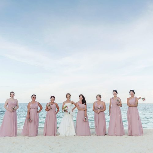 Bridesmaids on beach with ocean in background at Excellence Playa Mujeres