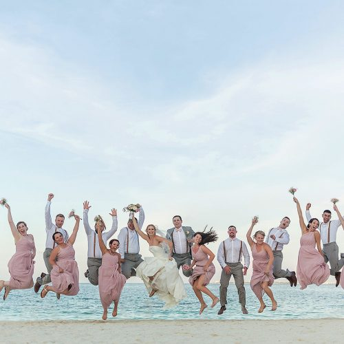 Bridal party jumping on beach after wedding at Excellence Playa Mujeres