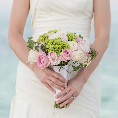 Close up of bridal bouquet with ocean in background
