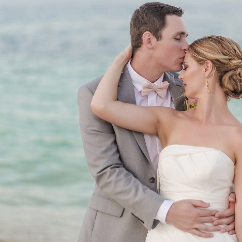 Bride and groom kissing on beach after wedding