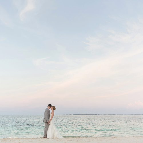 Bride and groom on beach at Excellence Playa Mujeres