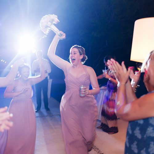 Bridesmaid catching bouquet at wedding reception.