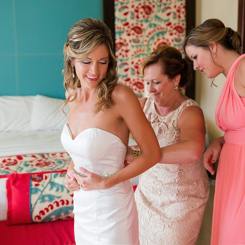 Mother of bride helping bride put on dress at NOW Jade Riviera Cancun