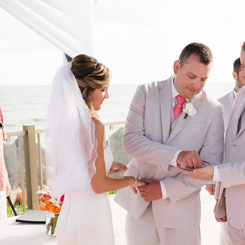 Groom putting on brides ring at pergola wedding location at NOW Jade Riviera Cancun wedding