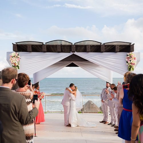 Bride and groom kiss under the pergola at Gazebo wedding location at NOW Jade Riviera Cancun