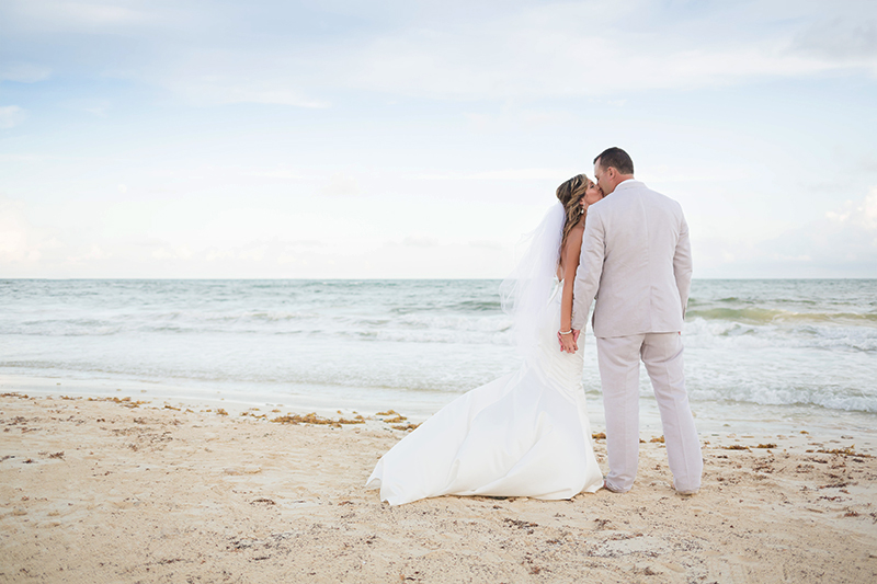 Bride and groom kissing on beach after wedding in Cancun.