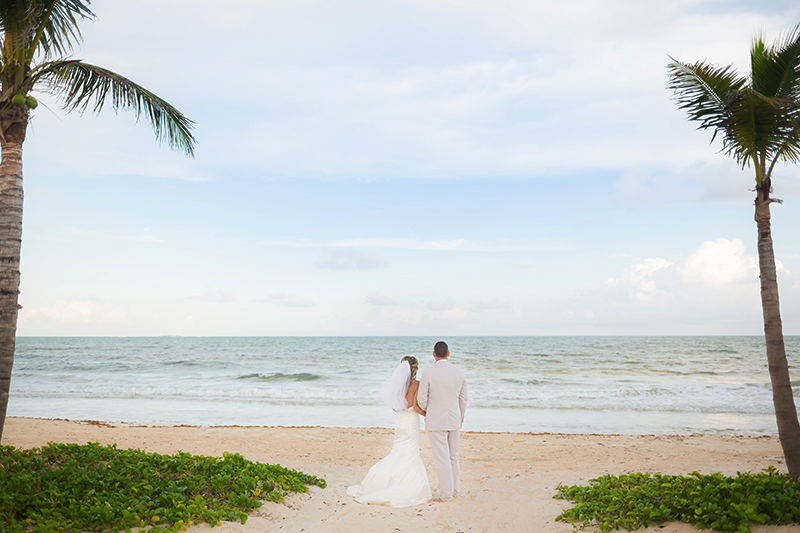 Bride and groom with Palm trees on beach near Cancun