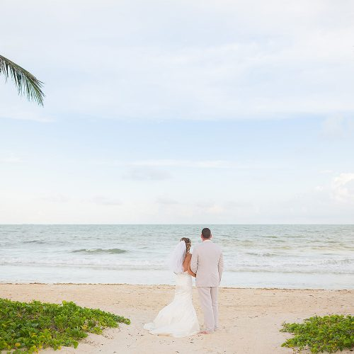 Bride and groom facing ocean under palm trees at NOW Jade Riviera Cancun wedding