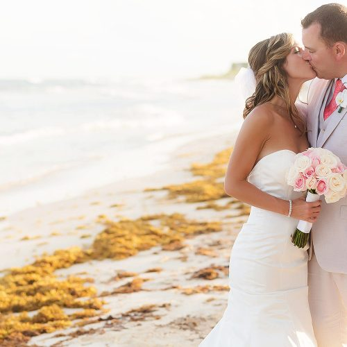 Bride and groom kissing on beach at NOW Jade Riviera Cancun wedding