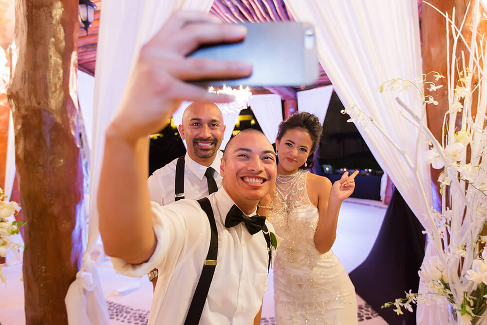 Bride and groom taking selfie with guest at wedding in Riviera Maya, Mexico