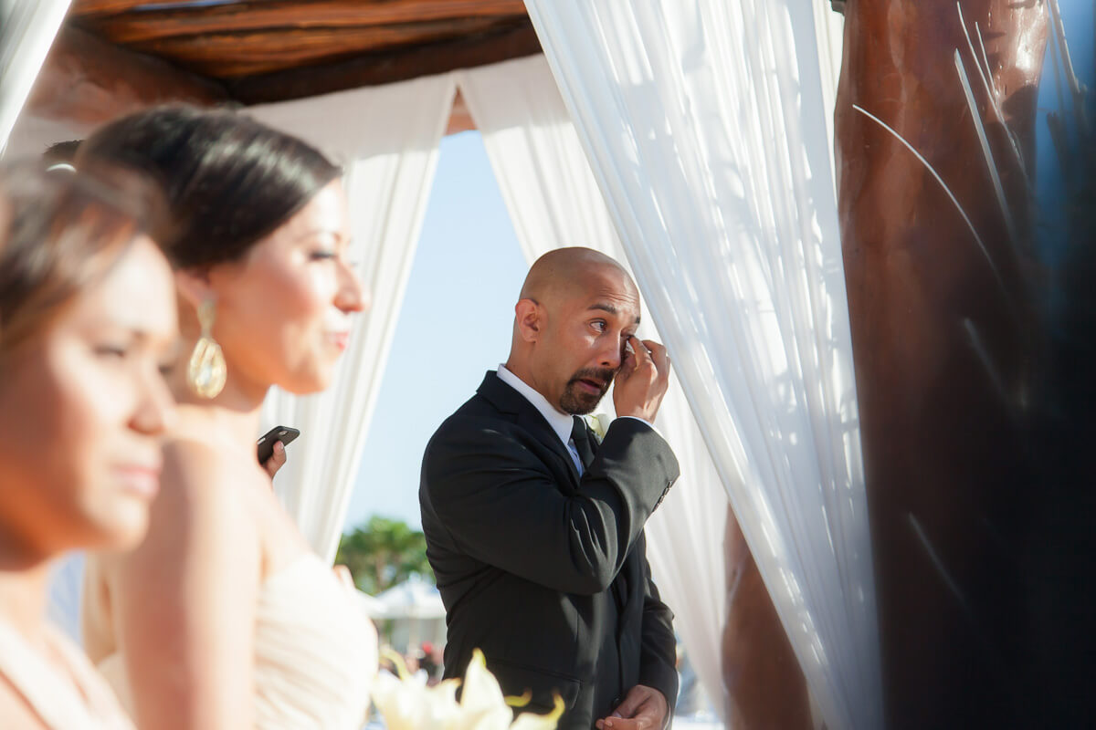 Groom crying as bride walks down aisle at wedding
