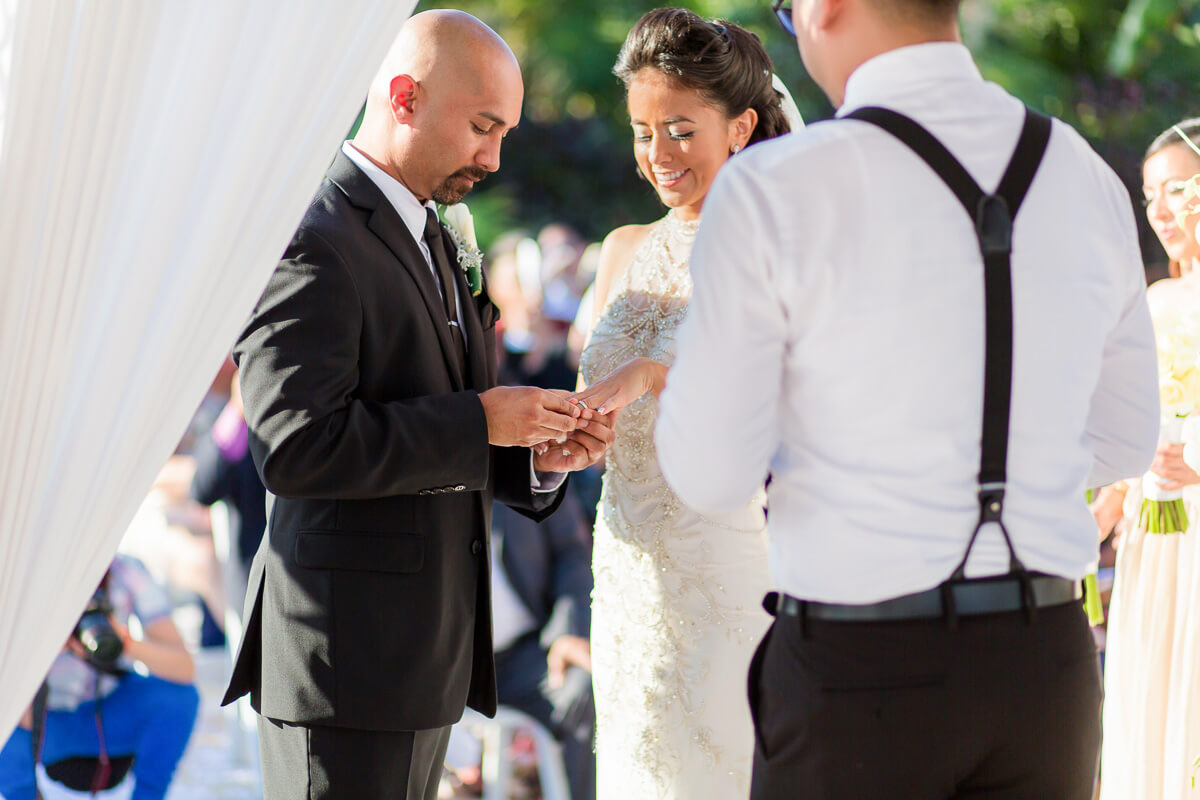 Groom putting on brides ring at wedding ceremony