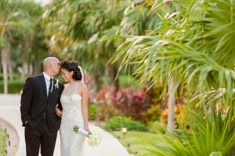 Groom kissing bride at Secretes Maroma Riviera Cancun