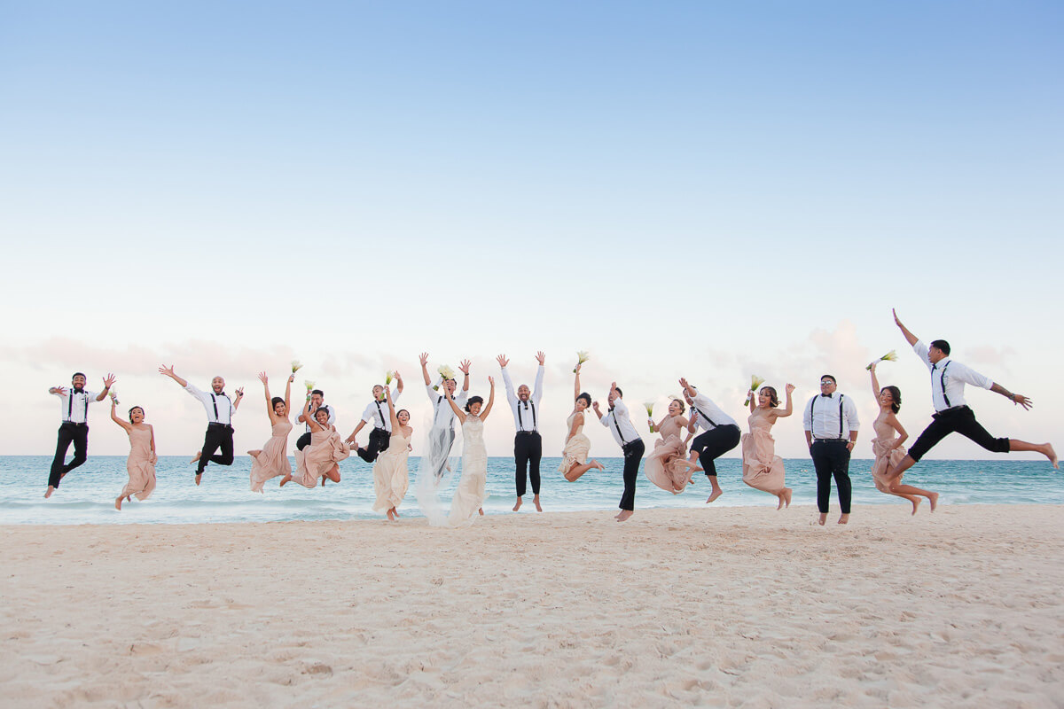 Bridal party jumping on beach at Secrets Maroma