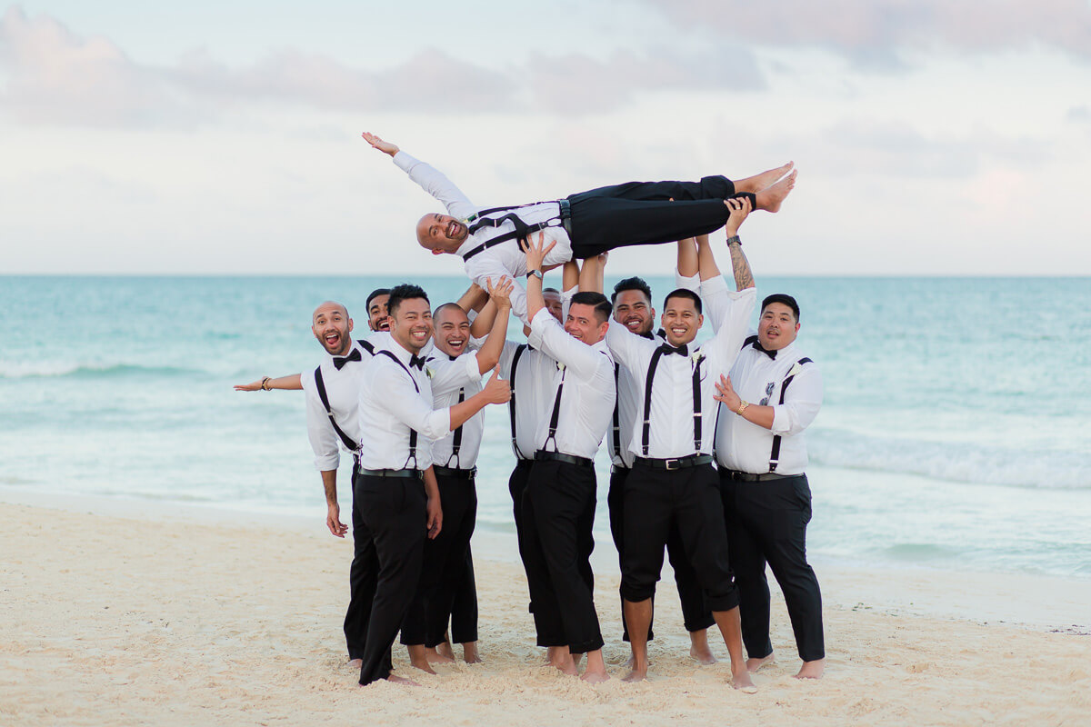 Groomsmen holding groom on beach at Secrets Maroma