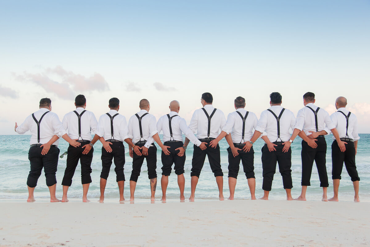 Groomsmen all holding each others bums on beach at Secrets Maroma