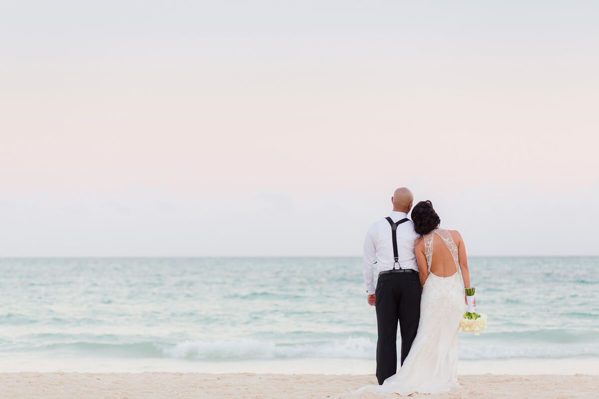 Bride and groom looking away on beach at Secrets Maroma
