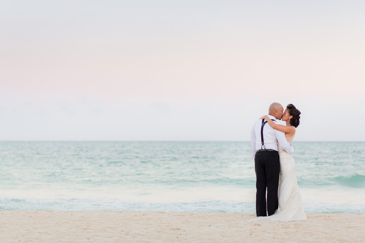 Bride kissing groom on beach at Secrets Maroma