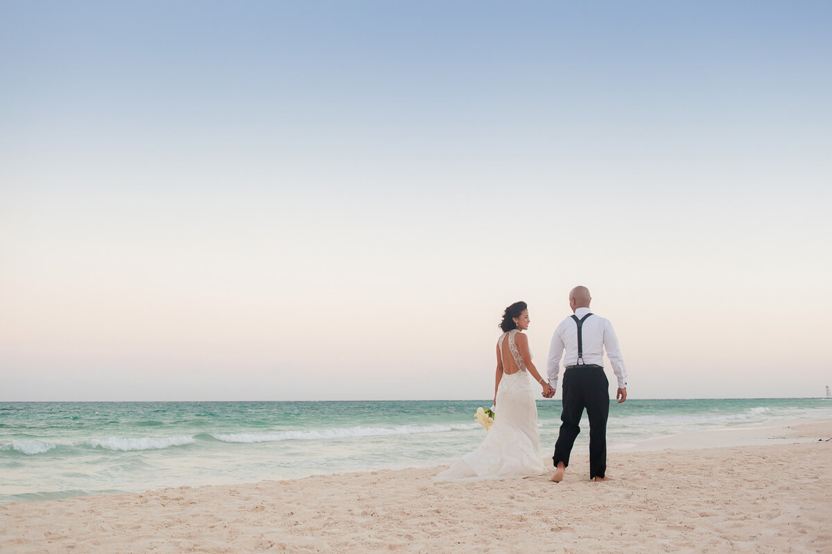 Bride and groom walking away on beach at Secrets Maroma